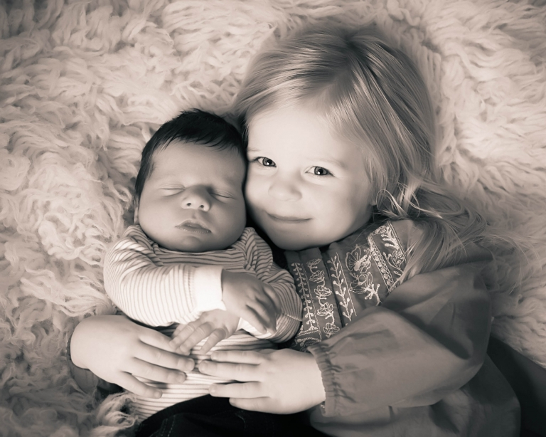 sister holds newborn baby brother portrait carmel, indiana