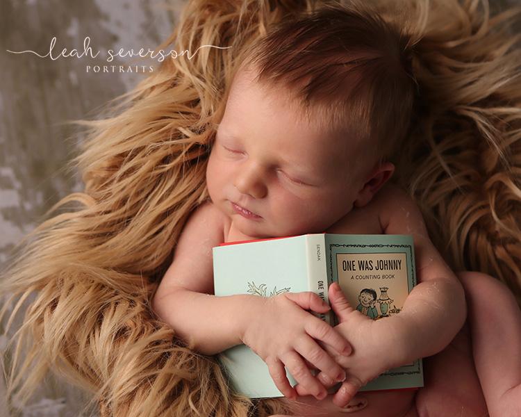 newborn-holding-book-prop-carmel-indiana