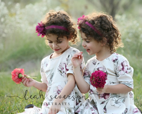 children laila and nicole smell flowers in carmel, indiana with professional photographer