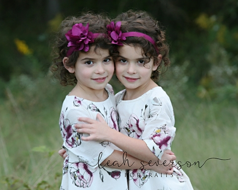 sisters hug during professional portrait session wearing purple headbands in carmel, indiana