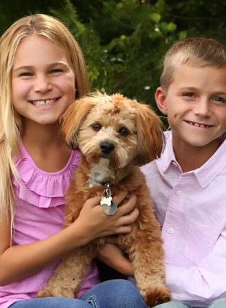 children posing with cute dog for family portrait