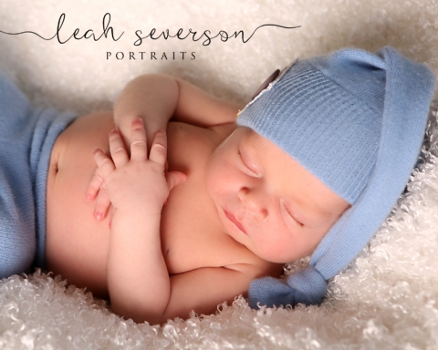 sleeping newborn baby wearing blue hat
