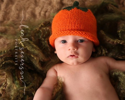 newborn camden's photograph with pumpkin hat