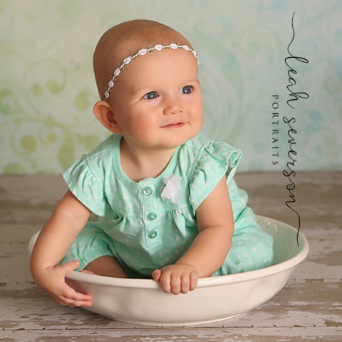baby charlotte sitting in bowl during portrait sessino