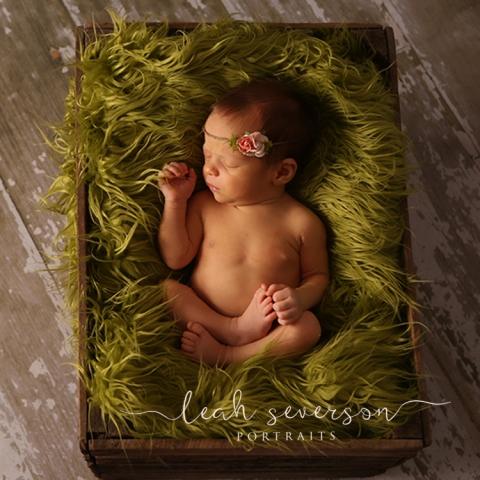 newborn baby sleeping on green furry blanket
