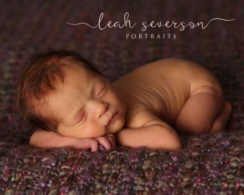 sleeping newborn baby on purple blanket