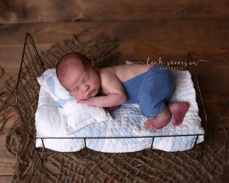 newborn sleeping on wire baby bed
