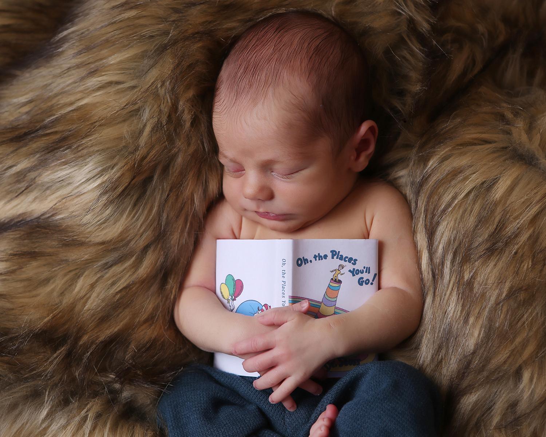 newborn baby holding book