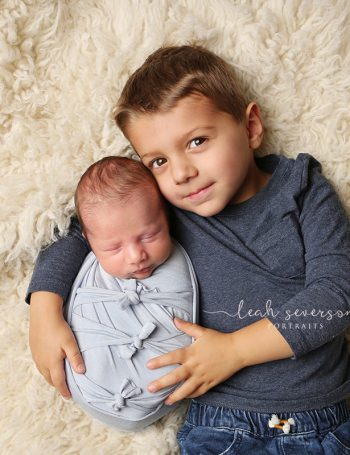 newborn baby boy in blue with brother photograph indianapolis